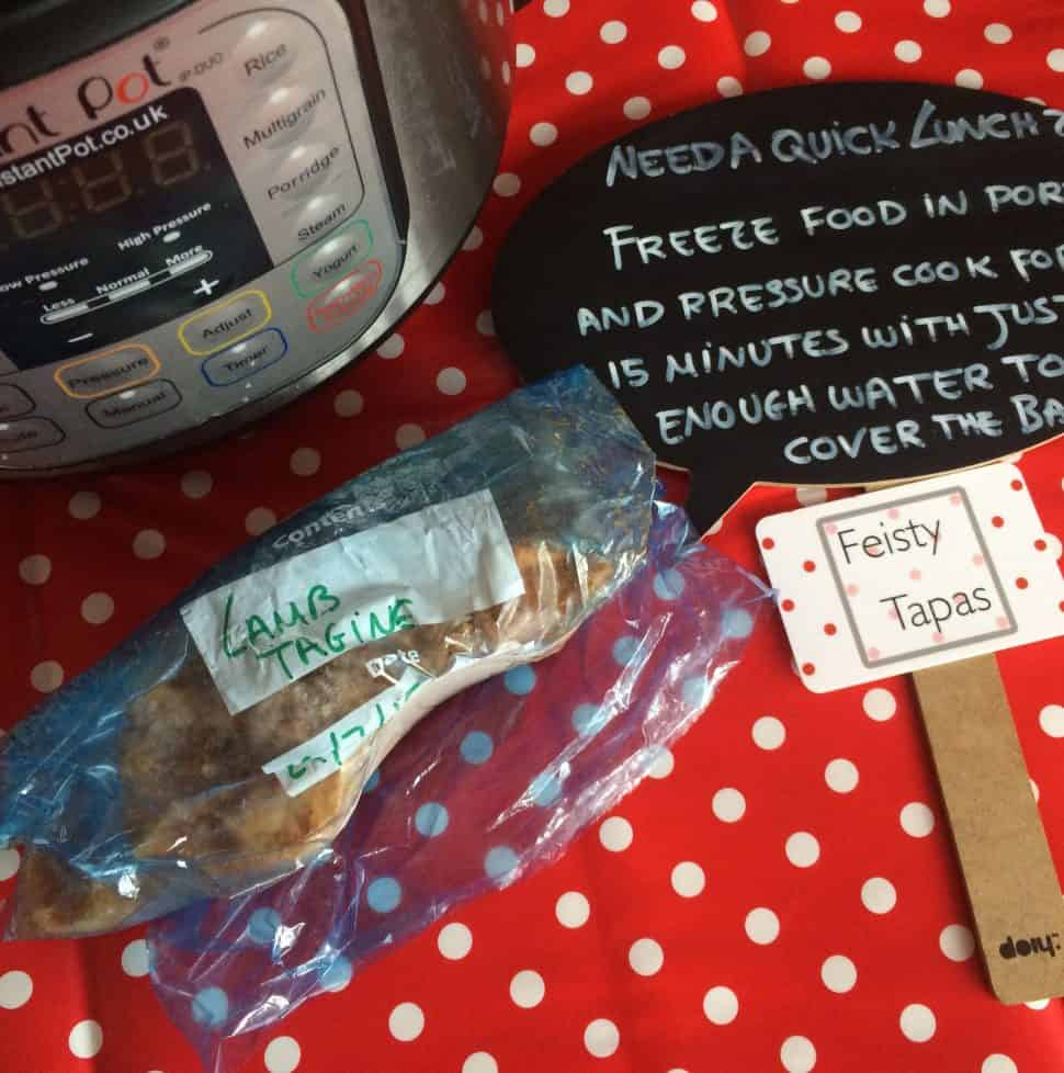 How to reheat from frozen in the Instant Pot. Instant Pot DUO and block of frozen food in plastic bag on a red and white polka dot spotty tablecloth. A chalkboard sign gives the instructions
