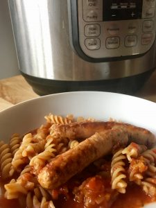 Feisty Tapas All-in-One Pressure Cooker Sausage and Tomato Pasta served in a white deep plate on a wooden table with an Instant Pot DUO in the background