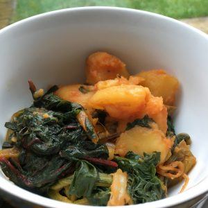 Chard and Potatoes cooked with paprika pressure cooked in the Instant Pot in no time. Served in a white bowl with green lawn / grass as the background. Photo set next to a big window