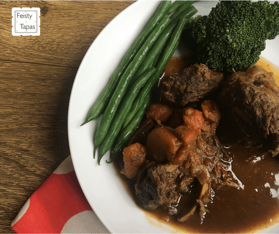 Delicious Feisty Tapas Instant Pot Pressure Cooker Ox Cheeks in Stout served with lots of sauce and green beans in a deep white plate with a wooden background and red and white polka dot fabric