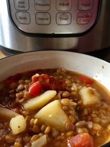 Instant Pot Spanish Lentil Soup (Lentejas) by Feisty Tapas served on a deep white dish with an Instant Pot DUO in the background. Green lentils, chorizo, potatoes... but it's super easy to make it a vegetarian or vegan lentil soup. Lentejas is a traditional Spanish Lentil Soup. An authentic Spanish dish