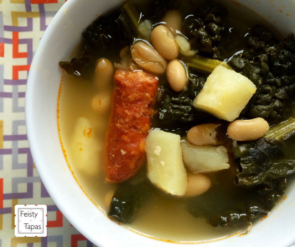 Instant Pot Soup with Greens, Beans, Potatoes Chorizo served on a deep white soup plate. This soup is based on the traditional Spanish Caldo Gallego, a delicious wholesome soup