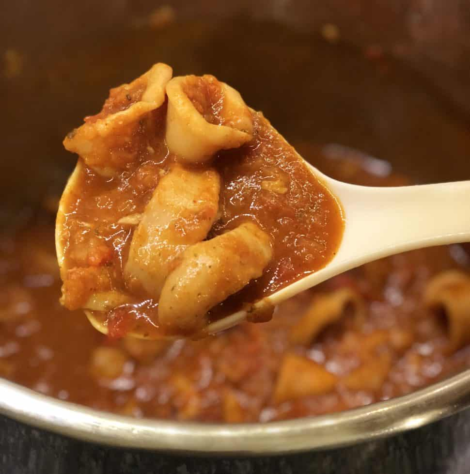 Instant Pot Squid Stew recipe by Feisty Tapas. Squid is really tender when pressure cooked and the sauce in this stew is delicious, with Spanish paprika hints. White ladle holding some of the stew with the Instant Pot's inner pot full of delicious Squid Stew in the background
