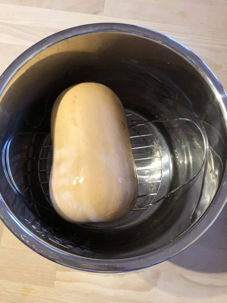 Whole butternut squash on the trivet of the Instant Pot ready to pressure cook to make peeling easier