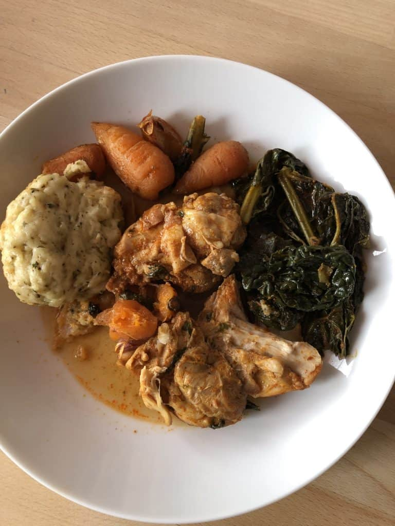 Instant Pot Chicken Stew with Dumplings on a white plate. Chicken thigh fillet, cavolo nero, carrot and dumpling. Wooden table as background