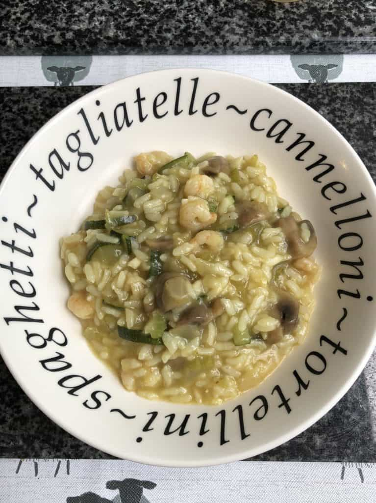 Delicious Instant Pot Prawn, Courgette and Mushroom Risotto served in a deep white plate with black wording. Recipe by Feisty Tapas. The perfect recipe for beginners with lots ot ftip