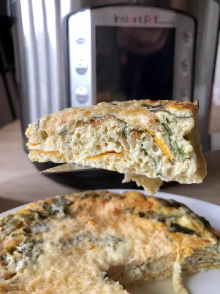 A slice of Instant Pot Chard and Sweet Potato Frittata with the Instant Pot Duo Evo Plus in the background