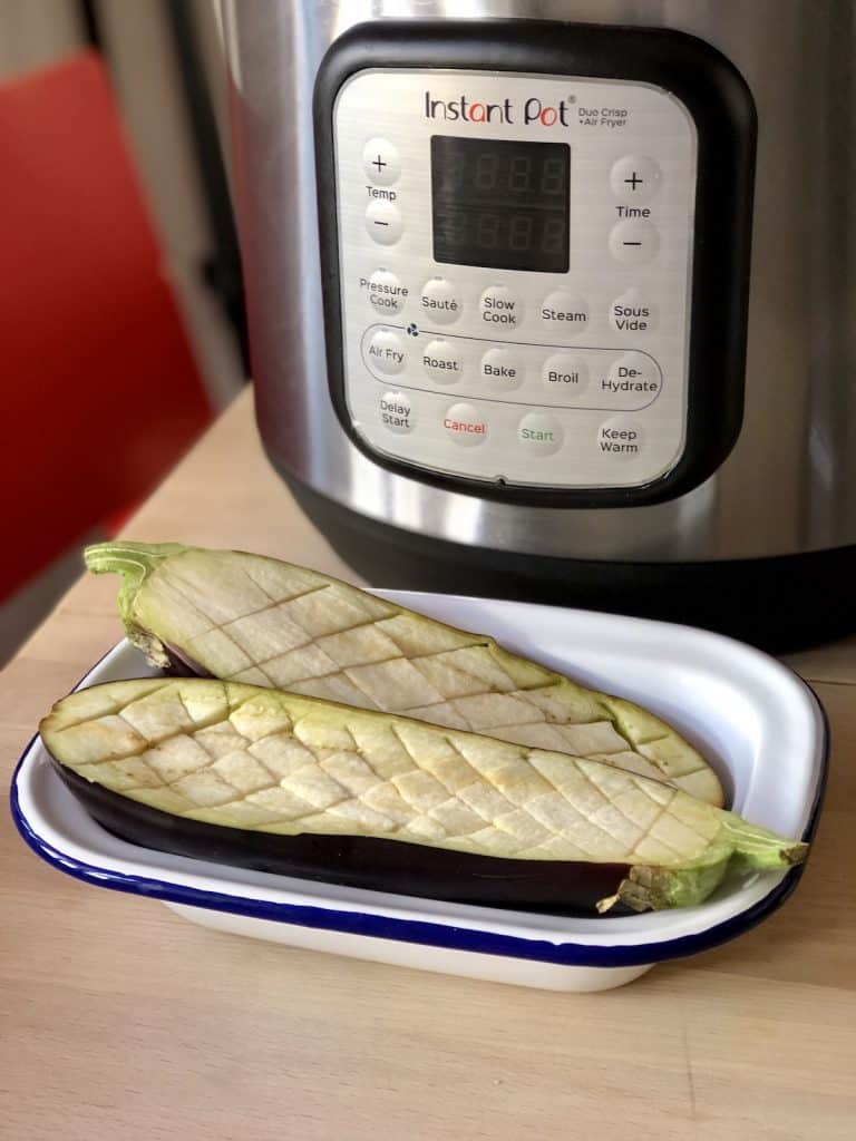 Aubergine sliced lengthways and with crisscross pattern ready to glaze in Instant Pot Duo Crisp