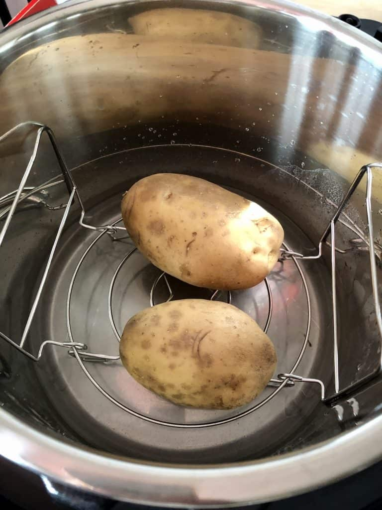 Instant Pot Duo Crisp jacket potatoes ready to cook on lower setting of trivet