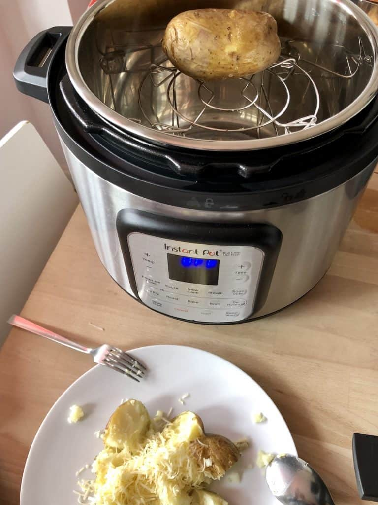 Instant Pot duo crisp baked potato view from above with potato still on trivet and other potato served with butter and cheese