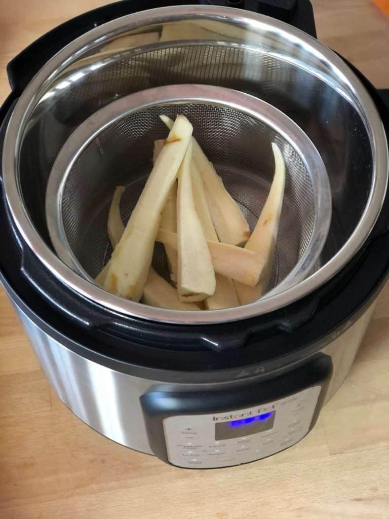 Prepared parsnips in mesh steamer basket in the inner pot of the Instant Pot Duo Crisp